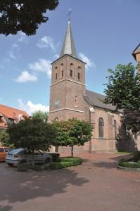 Der dreigeschossige  Turm mit Spitzhaube ist weithin zu sehen und überragt das Dorf.
